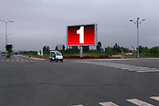 """A small police buggy drives past a large TV screen while patrolling otherwise empty streets in Kangbashi New District of Ordos City, Inner Mongolia, China on 16 August, 2011. With an investment of over 161billion USD from the local government and revenue from the region's rich coal deposits, enough buildings have risen on the site of an old desert village to hold at least 300,000 residents, complete with ultra modern facilities and grand plazas. The district however is less than 10% occupied, dubbed the """"ghost city"""", Kangbashi epitomizes China's real estate bubble and dangers in mindless investment fueled economic  growth. In 2011, the real estate price of Ordos city has dropped over 70%."""