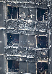 © Licensed to London News Pictures. 18/06/2017. London, UK. A bathroom (centre left) and Kitchen appliances (R) and the burnt exterior of Grenfell tower block are seen. The blaze engulfed the 27-storey building killing dozens - with 34 people still in hospital, many of whom are in critical condition. The fire brigade say that they don't expect to find anyone else alive. Photo credit: Peter Macdiarmid/LNP