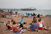 Crowds on Brighton Beach on a summer day enjoying the warm weather despite a mist coming in off the sea. Brighton, East Sussex.