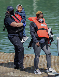 © Licensed to London News Pictures. 21/07/2021. Dover, UK. A young migrant is carried by Border Force officers as he is brought ashore at Dover Harbour in Kent after crossing the English Channel. It is being reported that at least 430 migrants crossed the English Channel to the UK on Monday, a new single day record. Photo credit: Stuart Brock/LNP
