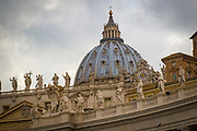 Saint statues on Saint Peter's Basilica roof edge facing the square, also the dome in the background
