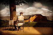 An older gentleman enjoys the view from the Montestigliano resort in Siena Italy.