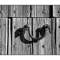 Old wooden door detail with old metal door handle knocker outside in the sunshine, Mallorca, Spain,