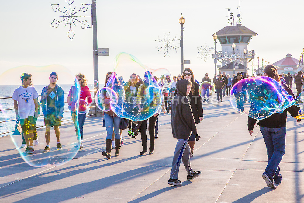 Bubbles Floating by People Walking on the Huntington Beach Pier