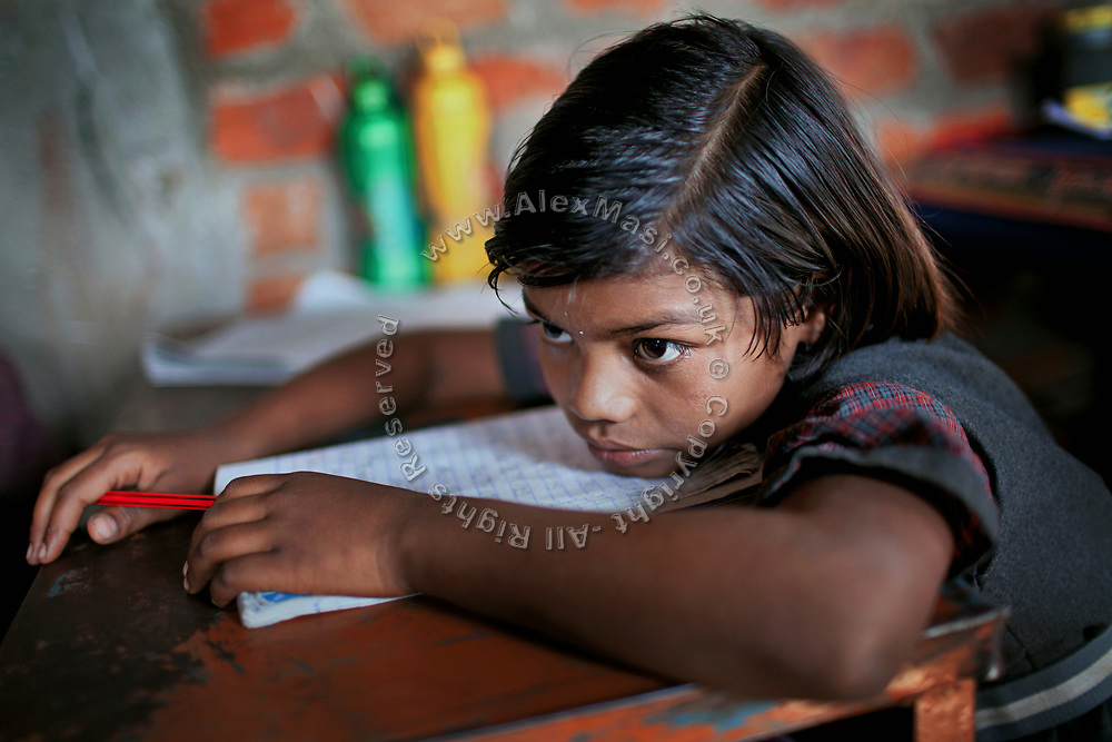 Poonam, 9, is leaning on her desk during a lesson in a cozy, private school located by her newly built home in Oriya Basti, one of the water-contaminated colonies in Bhopal, central India, near the abandoned Union Carbide (now DOW Chemical) industrial complex, site of the infamous '1984 Gas Disaster'.