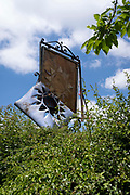 The sign for the Rising Sun pub, decays, on 13th June 2021, in Kemsing, Kent, England.