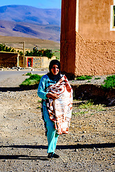 A young woman in traditional dress walking in the village of Tamtetoucht at the foot of the High Atlas in Morocco<br /> <br /> (c) Andrew Wilson | Edinburgh Elite media