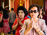 """07 FEBRUARY 2016 - BANGKOK, THAILAND: Women pray during Chinese New Year ceremonies at Wat Mangon Kamlawat in Bangkok. Chinese New Year, also called Lunar New Year or Tet (in Vietnamese communities) starts Monday February 8. The coming year will be the """"Year of the Monkey."""" Thailand has the largest overseas Chinese population in the world; about 14 percent of Thais are of Chinese ancestry and some Chinese holidays, especially Chinese New Year, are widely celebrated in Thailand.        PHOTO BY JACK KURTZ"""