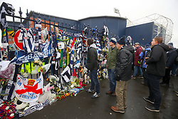 Fans look at tributes to Cyrille Regis ahead of the Premier League match at The Hawthorns, West Bromwich.