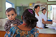 A young Nepalese baby looks over its mother's shoulder while being carried to the nurses station for a health review. They are in the Friends of Needy Children Nutritional Rehabilitation Centre, Kathmandu, Nepal.  The centre treats malnourished children and provides education to mothers about nutrition and childcare.