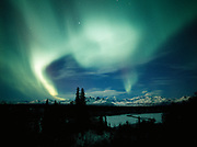 Beautiful display of northern lights over the Alaska Range including Mount McKinley or Denali with the Chulitna River in the foreground, Denali State Park, Alaska.