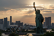 A replica of the Statue of Liberty stands near the Olympic rings monument on the Odaiba waterfront in Tokyo on June 22, 2021.
