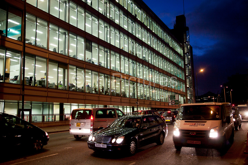 Cars and vans move along The Highway in East London in front of an office building lit up at night. This is one of the main artery roads out of London to the East. The Highway, formerly known as the Ratcliffe Highway, is a mile-long road in the East End of London, with several historic landmarks nearby. The route dates back to Roman times. In the 19th century it had a very notorious reputation for vice and crime and was the site of the infamous Ratcliff Highway murders.