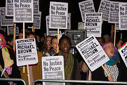 """London, November 26th 2014. A vigil for teenager Mike Brown who was shot dead by a policeman in Ferguson, Missouri this year, takes place outside the US embassy in London. Anti-racism and human rights campaigners called the 'emergency' protest following a court verdict that clears Police Officer Darren Wilson of murder. PICTURED: Placards raised, the crowd chants """"No justice, no peace!""""."""