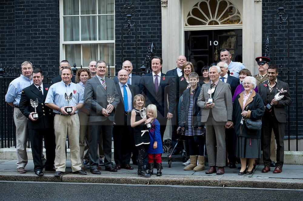 © London News Pictures. 30/10/2012. London, UK.  British Prime Minister David Cameron poses with winners of the Pride of Britain awards in front of 10 Downing Street on October 30, 2012. Pictured front are  sisters Ramona Gibbs (7) Trixie Gibbs (5). Ramona pushed her sister Trixie to safety from an oncoming car but sustained serious injuries herself.  Photo credit: Ben Cawthra/LNP