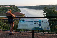 Foz do Iguazu, Brazil - March 28, 2019: A woman stands at the viewpoint at Marco das Tres Fronteiras, a popular tourist destination in the Brazilian city of Foz do Iguacu from which a visitor can view both Argentina (left) and Paraguay (right) at the confluence of the Parana and Iguazu Rivers.