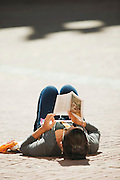 A young woman lies reading on the warm stone floor of the Palazzo del Campo, the main square in Siena, Tuscany, Italy