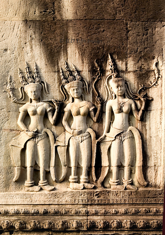 Angkor Thom: relief sculpture of three apsara dancers wearing triple conical headdresses and long skirts.