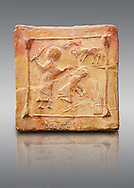 6th-7th Century Eastern Roman Byzantine  Christian Terracotta tiles depicting Abraham about to offer his son Isaac as a sacrifice<br />   - Produced in Byzacena -  present day Tunisia. <br /> <br /> These early Christian terracotta tiles were mass produced thanks to moulds. Their quadrangular, square or rectangular shape as well as the standardised sizes in use in the different regions were determined by their architectonic function and were designed to facilitate their assembly according to various combinations to decorate large flat surfaces of walls or ceilings. <br /> <br /> Byzacena stood out for its use of biblical and hagiographic themes and a richer variety of animals, birds and roses. Some deer and lions were obviously inspired from Zeugitana prototypes attesting to the pre-existence of this province's production with respect to that of Byzacena. The rules governing this art are similar to those that applied to late Roman and Christian art with, in the case of Byzacena, an obvious popular connotation. Its distinguishing features are flatness, a predilection for symmetrical compositions, frontal and lateral representations, the absence of tridimensional attitudes and the naivety of some details (large eyes, pointed chins). Mass production enabled this type of decoration to be widely used at little cost and it played a role as ideograms and for teaching catechism through pictures. Painting, now often faded, enhanced motifs in relief or enriched them with additional details to break their repetitive monotony.<br /> <br /> The Bardo National Museum Tunis, Tunisia.   Against a grey background.