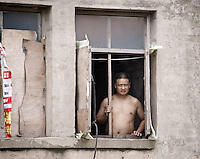 A suspicious looking man looking out a broken window in a village in rural China.