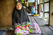 29 OCTOBER 2012 - MAYO, PATTANI, THAILAND:  NURIAH JETEH looks out from her house at the Bukit Kong home in Mayo, Pattani. The home opened 27 years ago as a Pondo School, or traditional Islamic school, in the Mayo district of Pattani. Shortly after it opened, people asked the headmaster to look after individuals with mental illness. The headmaster took them in and soon the school was a home for the mentally ill. Thailand has limited mental health facilities and most are in Bangkok, more than 1,100 kilometers (650 miles) away. The founder died suddenly in 2006 and now his widow, Nuriah Jeteh, struggles to keep the home open. Facilities are crude by western standards but the people who live here have nowhere else to go. Some were brought here by family, others dropped off by the military or police. The home relies on donations and gets no official government support, although soldiers occasionally drop off food. Now there are only six patients, three of whom are kept chained in their rooms. Jeteh says she relies on traditional Muslim prayers, holy water and herbal medicines to treat the residents. Western style drugs are not available and they don't have a medic on staff.    PHOTO BY JACK KURTZ