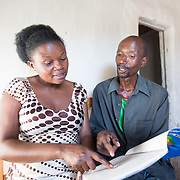 CAPTION: Gisèle (left) is a Field Worker for Service au Développement des Associations (SDA-IRIBA), Concern Worldwide's partner organisation. She knows Stanislas' case well, and can be seen here reviewing his financial plans. Before being selected as a beneficiary, Stanislas had served time in prison, which left him extremely poor and with severe financial problems. When he finally returned home, Stanislas found that everything had changed. His wife was now with another partner, and they had babies of their own. She had abandoned the land and home she'd once shared with Stanislas. He cleaned up his place as best he could, and made ends meet through daily wage labour and helping neighbours with odd jobs. He was depressed, feeling isolated and in conflict with his erstwhile wife. His children, who were being cared for by elderly relatives, returned, but he struggled to feed them, clothe them and send them to school. There were absolutely no resources with which he could make a new start. The community did try to help him in small ways, but lacking resources, he could not get access to the right information or guidance he needed to begin a new life. LOCATION: Rushikiri Village, Kimuna Cell, Rusatira Sector, Huye District, South Province, Rwanda. INDIVIDUAL(S) PHOTOGRAPHED: Gisèle Umumararungu (left) and Stanislas Iriboneye (right).