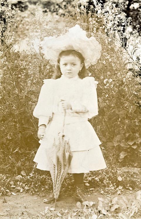 vintage deteriorating portrait of little child in garden setting