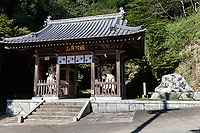 Senyuji Temple Gate - Senyuji  is No. 58 on the Shikoku pilgrimage and one of the more impressively located pilgrimage templesstandingon a hillside 1,300 feet above sea level which means that pilgrims who walk to it have quite a climb. The guardian statues in the gateway below the temple are impressive. Behind the daishi-do is a flight of concrete steps which leads up into the hill behind the temple. This path passes through pleasant woods of evergreen and trees including sasa bamboo. It's lined at intervals with attractive Buddhist statues. The path leads to a hilltop with panoramic views of Imabari, the Shimanami-Kaido suspension bridge and the Seto Inland Sea. For this walk, sensible shoes are a must. Sadly In 1947, all of the buildings built by Kobo Daishi between810-824 burned down in a forest fire. They were rebuilt from 1953. Senyu-ji is one of six pilgrimage temples located relatively close together in Imabari.
