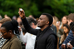 © Licensed to London News Pictures. 03/08/2021. LONDON, UK.  A man holding a candle during a minute silence at a vigil at Barn Hill Pond, Fryent Country Park near Wembley to remember the lives of sisters Bibaa Henry and Nicole Smallman, on what would have been Nicole's 29th birthday.  The sisters were murdered in the park in June 2020 whilst celebrating Bibbaa's birthday.  Reclaim These Streets have worked with former Archdeacon of Southend, the Ven. Wilhelmina (Mina) Smallman, the late sisters' mother, to organise the vigil and attendees were encouraged to wear green and purple, the sisters' favourite colours, or light a candle.  Photo credit: Stephen Chung/LNP