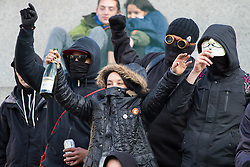 "London, April 16th 2016. A young woman clutches a bottle of cava as anarchists let off a smoke bomb on the plinth of Nelson's column in Trafalgar Square after thousands of people supported by trade unions and other rights organisations demonstrated against the policies of the Tory government, including austerity and perceived favouring of ""the rich"" over ""the poor""."