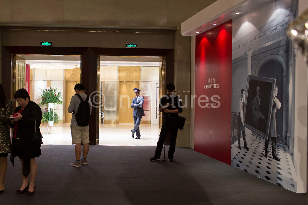 """A Christie's doorman stands in front of the entrance to Christie's very first mainland China auction in Shanghai, China September 23,  2013. Both Southeby's and Christie's have opened an office in Mainland China in the past year, however they face overwhelming odds as China's state-owned auction houses such as Poly and Jiamu enjoys a near monopoly over China's art procurement market as foreigners are not allowed to buy vaguely defined """"historical"""" art."""