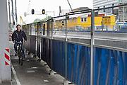 Een fietser rijdt over een heel smal tweerichtingenfietspad tussen een hek en een betonpaal in het stationsgebied van Utrecht, waar veel werkzaamheden plaatsvinden. <br /> <br /> A cyclist rides on a very narrow two-way cycle path between a fence and a concrete pile in the station area of Utrecht, where many activities take place.