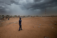 A police officer shields her self from the a gust of wind in Juba, the capital. The region still has few police officers, and most are soliders who have just be given blue uniforms.