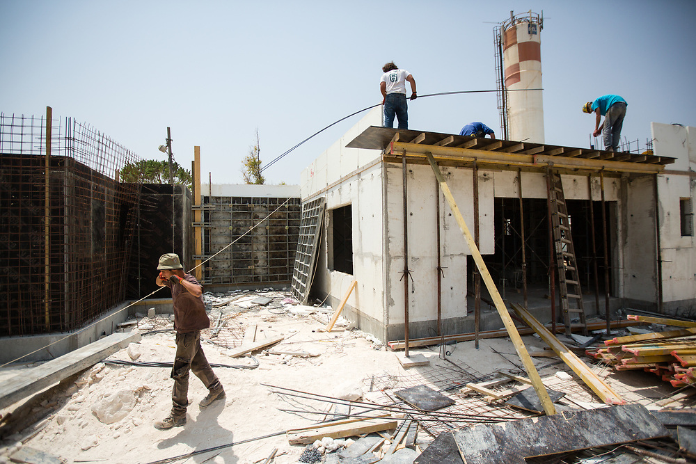 Jewish Israeli laborers are seen during work at a construction site in the West Bank Jewish settlement of Yitzhar, south of the Palestinian West Bank city of Nablus, on August 5, 2015.