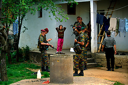 MARZIC, KOSOVO - MAY 7, 2002 - KFOR NATO peace keeping forces conduct a routine search for weapons in an Albanian Muslim village in northern Kosovo. Civilians and combatants an all sides of the conflict were given a deadline to voluntarily hand in their weapons. Since then, peace keeping forces routinely search homes for weapons. (PHOTO © JOCK FISTICK).