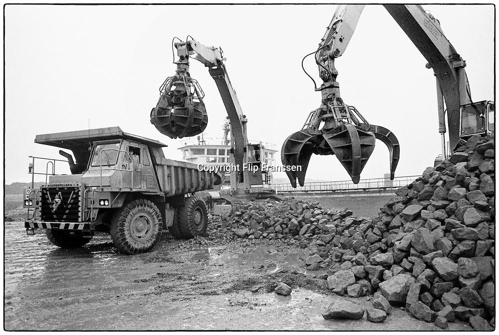 Nederland, Zeeland, 15-1-1986<br /> De hoogwaterkering, stormvloedkering, oosterscheldekering in de Oosterschelde in de eindfase voor de oplevering. In oktober zal de opening, ingebruikname plaatsvinden. Basaltblokken worden geladen op kiepwagens<br /> Foto: Flip Franssen/Hollandse Hoogte