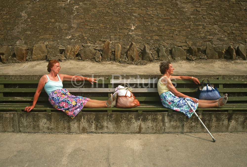 Two sisters sit in identical poses on sea wall benches at Blackpool's Promenade, Lancashire, England. The eccentric pair has adopted the same posture in a way that twins and sisters sharing the same genetic characteristics and habits often do. Seated with bags at their own sandals and with the same styles of floral pattern dresses, the two look like the proverbial 'peas in a pod.' Blackpool is a seaside resort in the northwest of England is diverse in its transient holiday population whose behaviour can be routinely odd. Blackpool is the largest resort in the north of England and visited traditionally by working people during the industrial revolution.