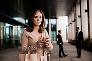 Business woman using her smart phone outside Gaspe House corporate offices in St Helier Jersey, CI
