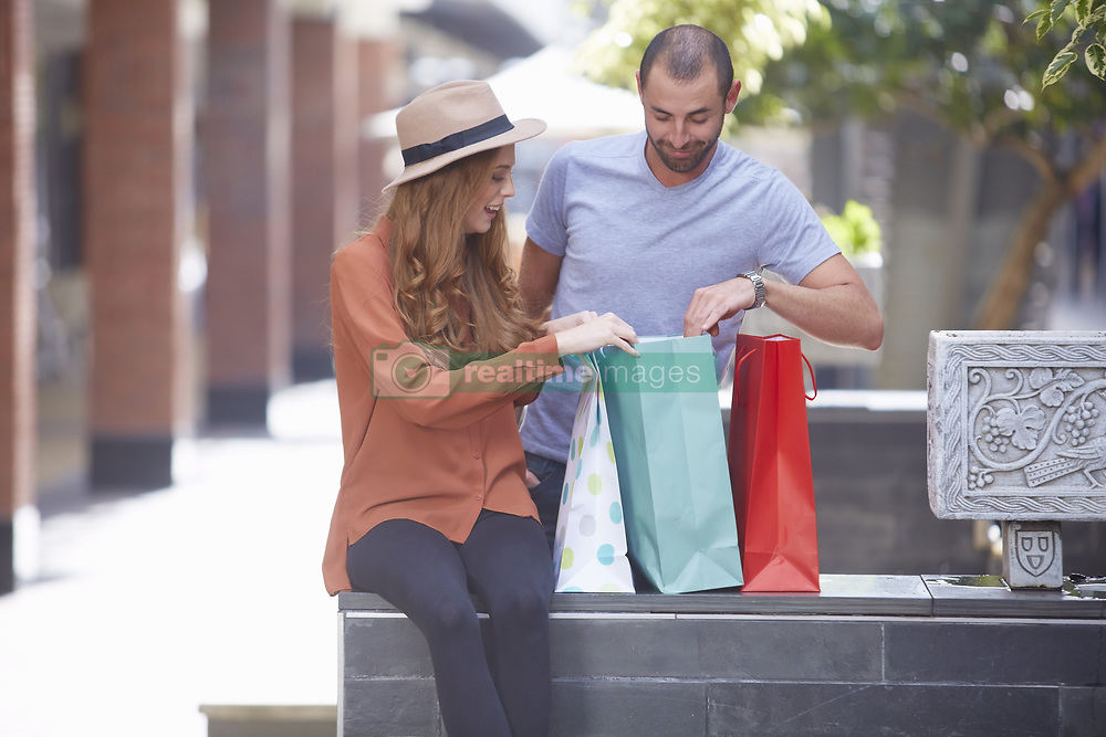 Jan. 13, 2015 - Young woman sitting on wall with shopping bags, man looking in bags (Credit Image: © Image Source/Image Source/ZUMAPRESS.com)