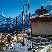 A trekker passes a Tibetan Buddhist chorten and prayer flags in Khumjung village in the Khumbu region of Nepal's Himalaya. 1979 photo. Mount Ama Dablam background.
