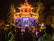 04 OCTOBER 2014 - GEORGE TOWN, PENANG, MALAYSIA: A chariot drawn by blessed oxen carries Hindu priests and the Durga deity through the streets of George Town during the Navratri procession. Navratri is a festival dedicated to the worship of the Hindu deity Durga, the most popular incarnation of Devi and one of the main forms of the Goddess Shakti in the Hindu pantheon. The word Navaratri means 'nine nights' in Sanskrit, nava meaning nine and ratri meaning nights. During these nine nights and ten days, nine forms of Shakti/Devi are worshiped.   PHOTO BY JACK KURTZ