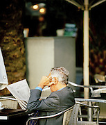 A businessman sitting outside, reading the newspaper, at a cafe in Barcelona, Spain