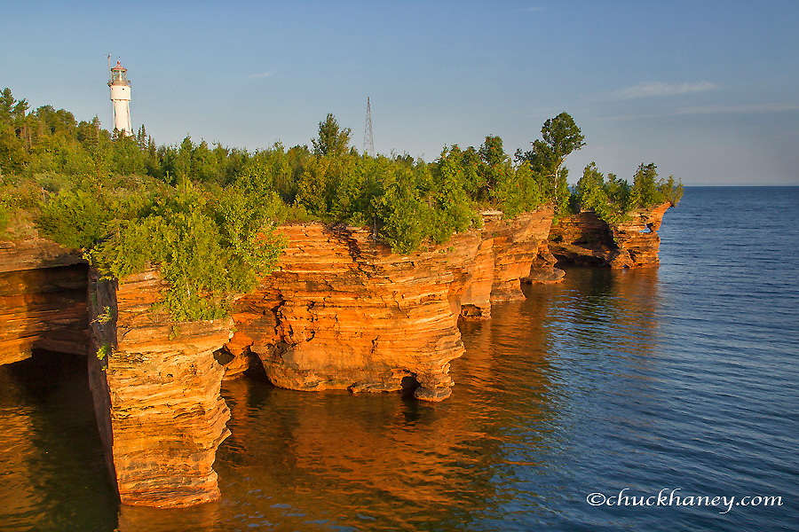 Layered sandstone cliffs and sea caves at sunrise on Devils Island Lighthouse in the Apostle Islands National Lakeshore, Wisconsin, USA