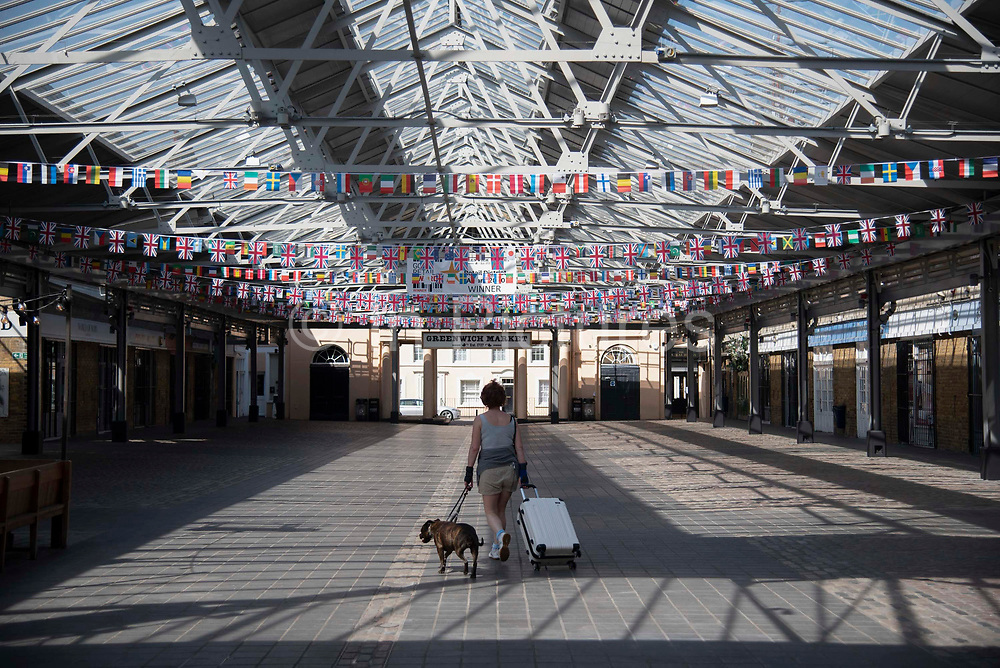 A women walks through an empty Greenwich Market with a dog and suitcase on 15th April 2020 in Greenwich, London, United Kingdom. Chancellor of the Exchequer, Rishi Sunak has said the Office for Budget Responsibility OBR, the UKs tax and spending watchdog suggests the coronavirus crisis will have serious implications for the UK economy, warning the pandemic could see the economy shrink by a record 35% by June, increasing unemployment by over 2 million and sending the budget deficit to its highest since World War II.