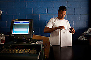 ALLENTOWN, PA – JUNE 4, 2011: Amaro Zucasta prepares to reload a printer at Quality Auto Shop in Allentown, where he is employed as a vehicle inspector. Zucasta immigrated to the United States from the Dominican Republic when he was nine.<br /> <br /> As the population of second and third generation Hispanics increases dramatically in the United States, a new boldness can be sensed among Latinos in America, stretching far beyond the southern border states. Demographers in Pennsylvania say the towns of Bethlehem, Allentown and Reading are set to become majority-minority cities, where Hispanics comprise a bigger portion of the population than whites. As this minority population increases dramatically in the region, Latinos are inching closer to their own realization of the American Dream, while gradually shifting the physical and cultural landscapes of their communities.