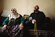Mehemet Çinar, 81, photographed here with his wife Emine, 78, fingers his prayer beads and prays throughout the day, in addition to the required 5 times a day for the Muslim faithful. He is largely bed bound with lung ailments, but still smokes regularly. Golden Horn (or Haliç) area, Istanbul, Turkey.