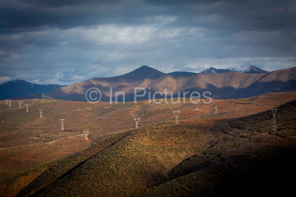 Winter sun shining over the electricity pylons that travel across the mountains that are used to transfer power from the Fierze Hydroelectric Power Station in Northern Albania on the 12th of December 2018, Albania. The power station dam has a total volume of 8 million cubic meters and has an annual average power output of 1,330GWh.