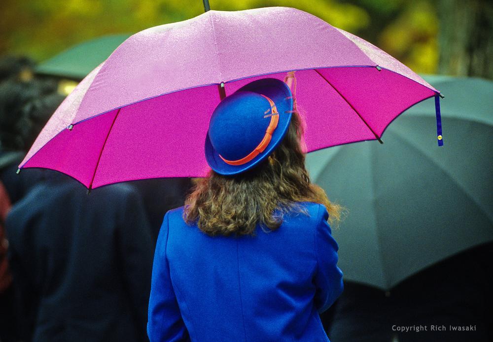 Female tour guide in blue uniform waits with an umbrella at Hiroshima Peace Park, Hiroshima, Japan