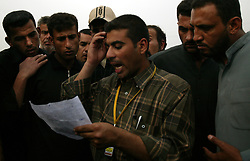 Relatives listen for possible names of injured loved ones as a hospital worker reads them aloud outside Al-Kadhimiya Teaching Hospital, Baghdad, Iraq, March 2, 2004. At least two suicide bombers blew themselves up outside of Al-Kadhimiya Mosque in Baghdad, where thousands of Shia Muslims had gathered to celebrate the Ashura religious festival. In what coalition authorities said was a coordinated attack, several bombs exploded in the holy city of Karbala as well, where an estimated two million Shias from Iraq, Iran, Pakistan and as far away as Canada had gathered for the holiday, which commemorates the martyrdom of Imam Hussein, grandson of the Prophet Mohammed. At least 143 people were killed in the combined attacks.