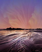 Photographic artwork of hibiscus flower in the sky above the patterns etched in the sand at sunset on the Oregon Coast